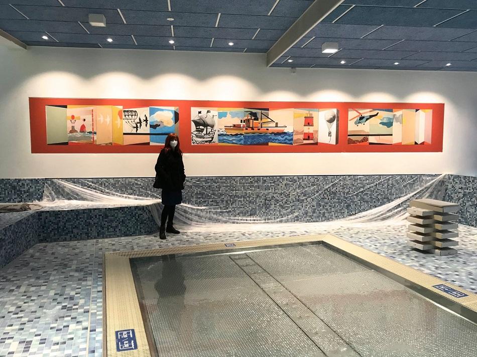 Braunschweig, Heidbergbad, Jessica Reinjes 2021 im Neubau vor dem Reprint des Wandbilds ihres Vater Peter Voigt (Bild: privat, 2021)