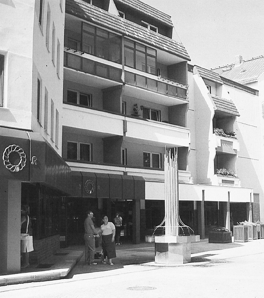 Auf diesem zeitgenössischen Foto wird nicht nur die Bewunderung für die kunstvolle Straßenmöblierung visualisiert. Deutlich wird die sehr belebte und differenzierte Fassadengestaltung. Viele von diesen Differenzierungen ergaben sich nahezu automatisch, indem man den Anschluss der Neubauten an die bestehenden Gebäude plante (Architektur der DDR 1/89, S. 14).