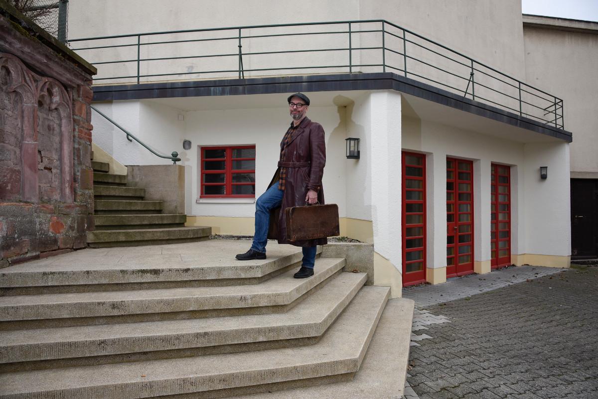 Frankfurt-Niederursel, Daniel Bartetzko mit historischem Mantel und Koffer vor der Gustav-Adolf-Kirche (Foto: Andreas Beyer)