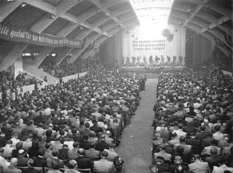 """Magdeburg, Ausstellungshalle """"Land und Stadt""""/Hermann-Gieseler-Halle (J. Göderitz, 1924), Konferenz der Wählervertretung, 1954 (Bild: Bundesarchiv Bild 183-26465-0001, CC BY SA 3.0.de, Foto: I. Biscan)"""
