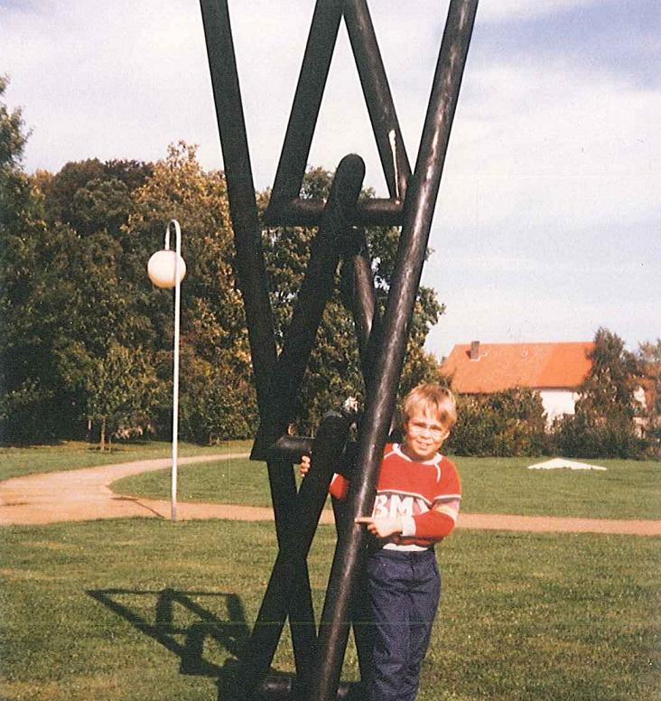 """Martin Bredenbeck 1984/85 vor einem hölzernen Kunstding: """"Das müsste der Skulpturenpark in Willebadessen sein. In der Gegend waren wir oft im Urlaub."""" (Bild: privat)"""